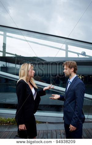Caucasian businesswoman serious speaking to a colleague while they standing outside office