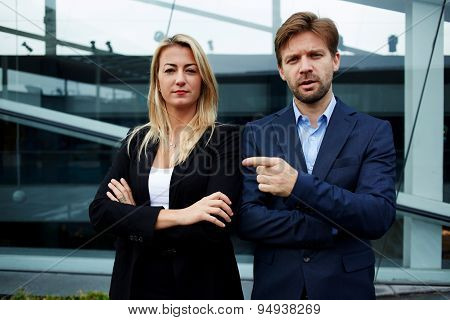 Experienced businessman friendly pointing with finger to his professional colleague