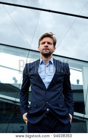 Low angle portrait of frustrated and worried businessman standing with his hands in his pockets