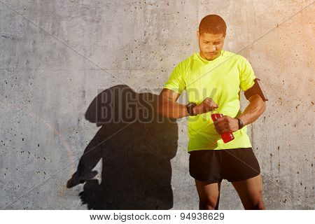 Young man resting after workout standing on concrete wall background at sunny afternoon