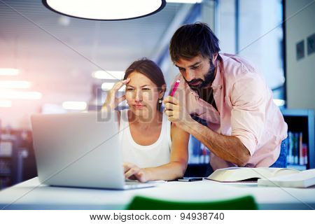 Male executive showing to employer things on laptop while they working in modern office