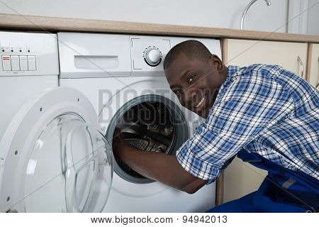 Young Male Technician Fixing Washing Machine
