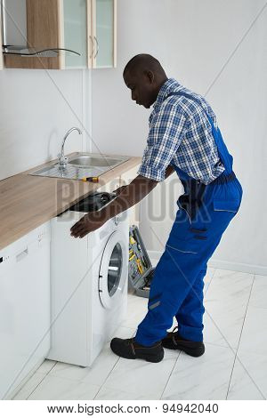 Technician Pulling Washing Machine In Kitchen