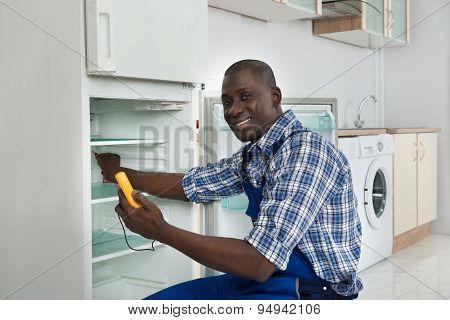 Technician Repairing Refrigerator Appliance