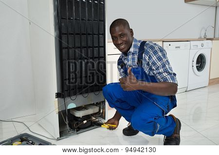 Technician Fixing Refrigerator