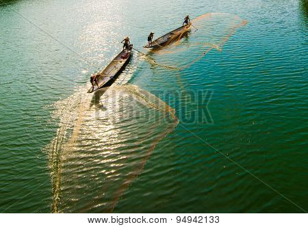 Fishermen are throwing fishing net on the river in Hue, Vietnam.