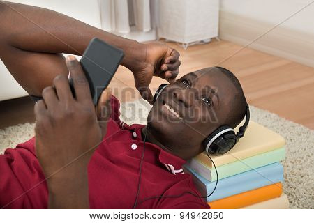 Man Lying On Stack Of Books Listening Music