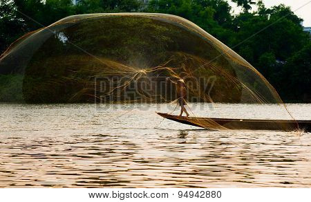 Fisherman is throwing fishing net in Hue, Vietnam