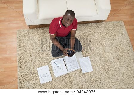 Man Calculating Invoices Using Calculator