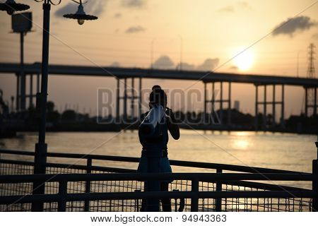 Sunset over water with girl looking through telescope