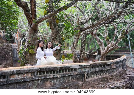 Vietnamese girls with Ao Dai in Tu Duc royal tomb in Hue, Vietnam