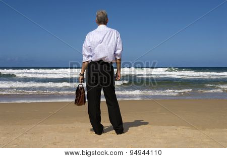 Businessman On Beach Relaxing Looking At Horizon