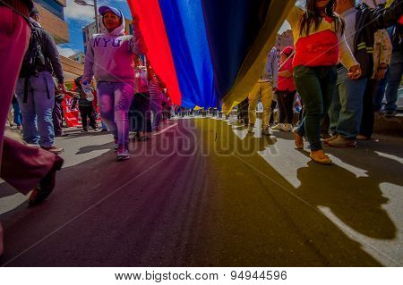 Street view from under giant ecuadorian flag during anti government march and protests in Quito