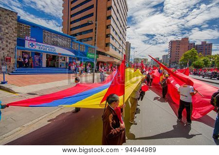 Protesters holding giant flag marching with ecuadorian and Union Popular flags in the capital city Q