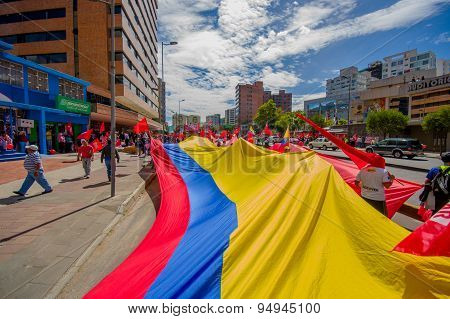 Very big Ecuadorian flag being carried through city streets as part of Union Popular party marching