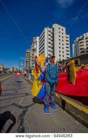 Ecuadorian flag salesman with varied selection standing in sunny street facing camera and showing me