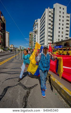 Ecuadorian flag salesman walking in sunny city street with various sizes for sale