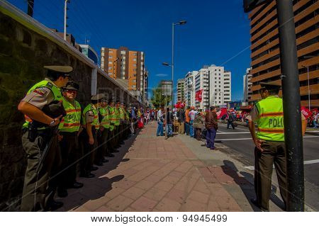 Long line of ecuadorian policemen supervising protesters from the party Unidad Popular marching in c
