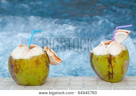 Coconut With Straws To Drink On The Side Of The Pool