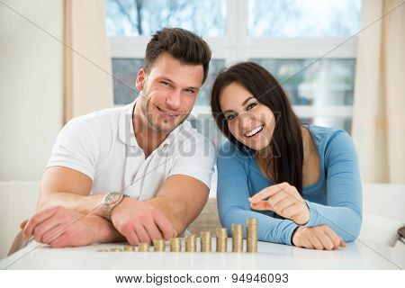 Happy Couple Arranging Stacks Of Golden Coins