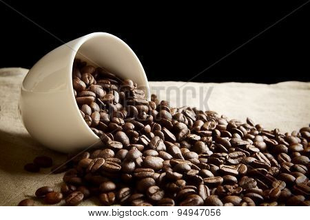 Strewn Beans Of Coffee From A Cup On Black And Flax