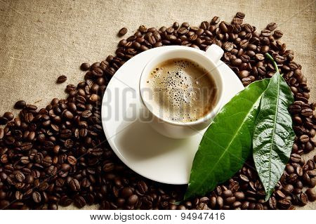 // Coffee With Foam Cup With Beans In The Corner With Green Leaf On Linen