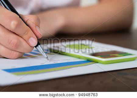 Businesswoman Analyzing Graph With Calculator