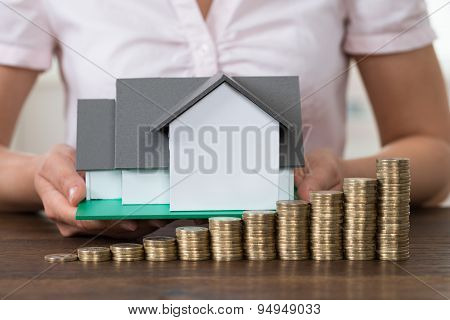 Businesswoman With House Model And Stack Of Coins
