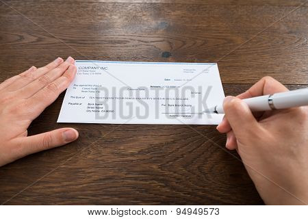 Person Hands Signing Cheque With Pen