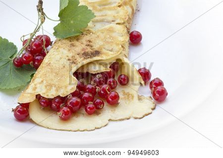 Pancake Or Crepe With  Red Currants On A White Plate