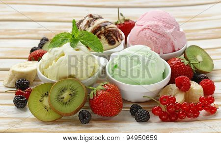 Assorted ice cream strawberry, banana, mint, chocolate and fresh berries on the wooden table