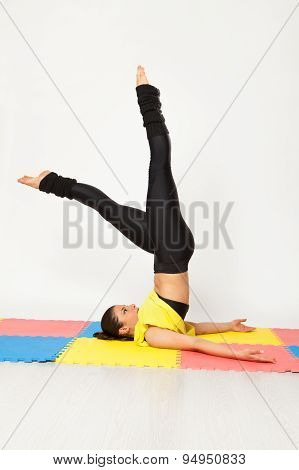 Sexy woman doing yoga exercises on a colorful carpet
