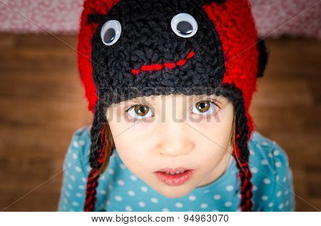 Portrait Of Little Girl Looking In The Camera. Child Is Wearing A Woolen Cap In The Shape Of Ladybir