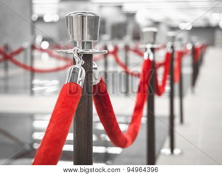 Red Carpet Fence Pole With Red Ropes Blurred Interior Background
