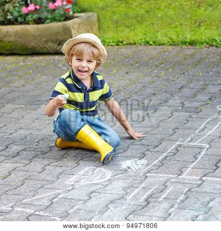 Little Boy Painting A Tractor Vehicle With Chalk In Summer