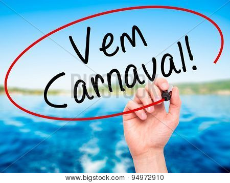 Man Hand writing Carnival is Coming (in Portuguese) with black marker on visual screen.