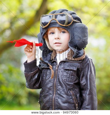 Happy Kid Boy In Pilot Helmet Playing With Toy Airplane