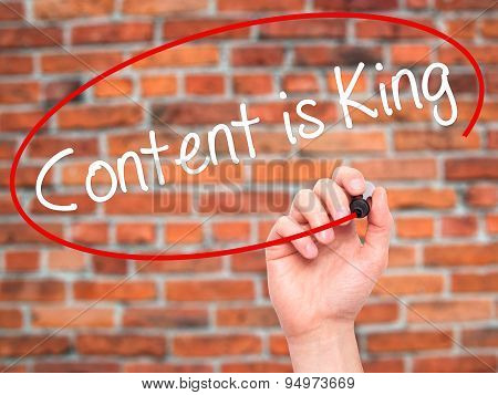 Man Hand writing Content is King with black marker on visual screen.
