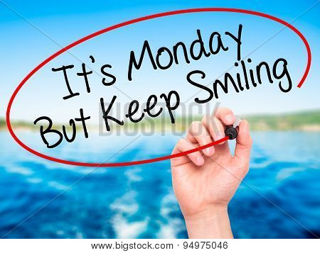 Man Hand writing It's Monday But Keep Smiling with black marker on visual screen.