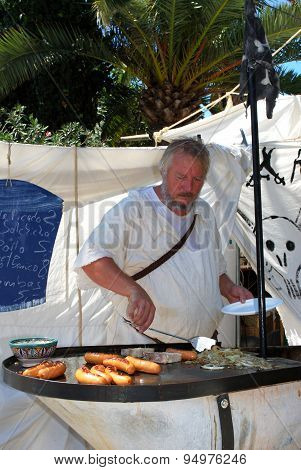 Chef cooking sausages on market stall, Spain.