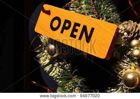 Wood sign say OPEN on the door