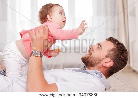 Vivacious father holding his kid in air