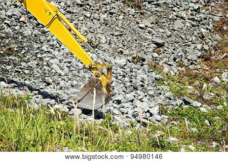 Excavator Shovel Digging Rock On Constriction Site