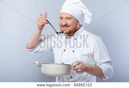 Head-cook tasting food from saucepan
