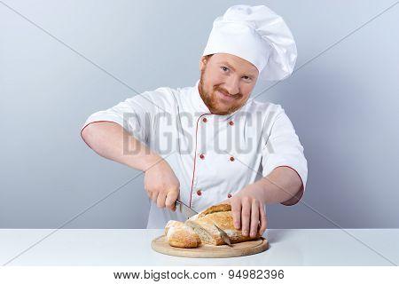 Head-cook slicing freshly baked bread