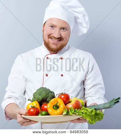 Head-cook holding big plate of fresh vegetables