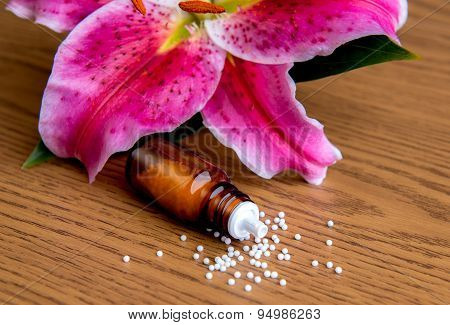Homeopathic Globules On Wooden Ground With Lilly