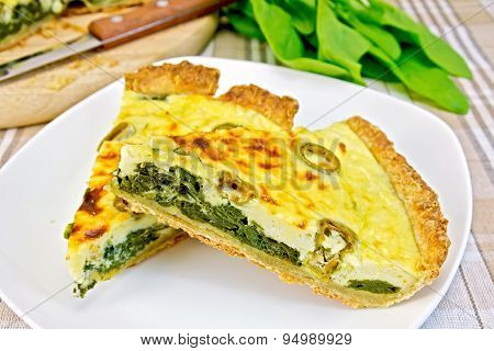 Pie with spinach in plate on fabric