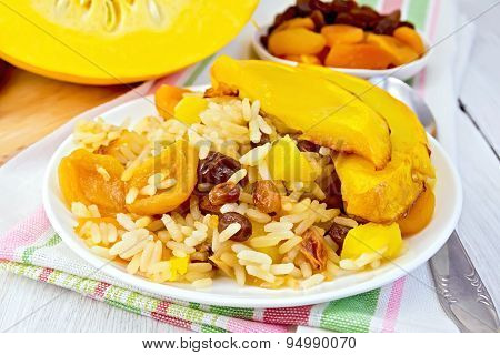 Pilaf fruit with pumpkin in white plate on board