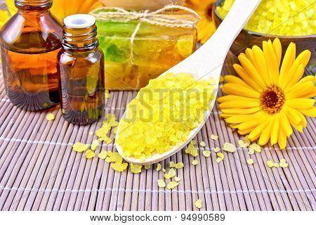 Salt yellow and oil with calendula on bamboo